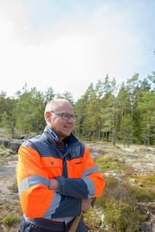 Портрет зрелого красивого скандинавского мужчины, готового к сбору урожая в лесу на открытом воздухе