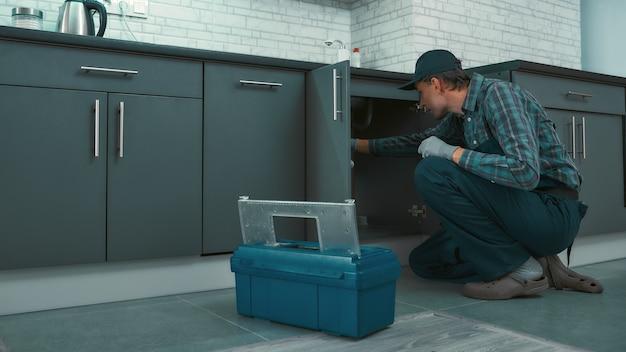 Портрет зрелого разнорабочего в униформе, проверяющей водопроводные трубы на кухне. горизонтальный снимок
