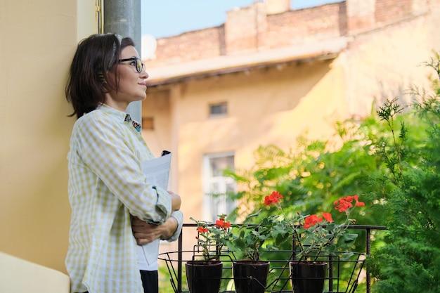 成熟した主婦の女性の肖像画、緑の植物、コピースペースで飾られたオープンバルコニーに雑誌と女性
