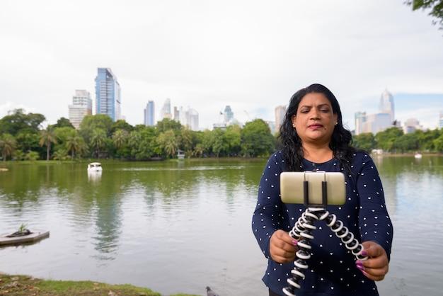 Портрет зрелой индийской женщины, расслабляющейся в парке