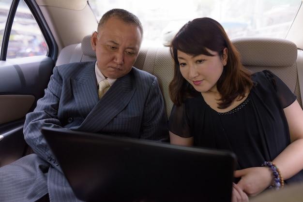 成熟した日本のビジネスマンとバンコクの街を探索する成熟した日本人女性の肖像画