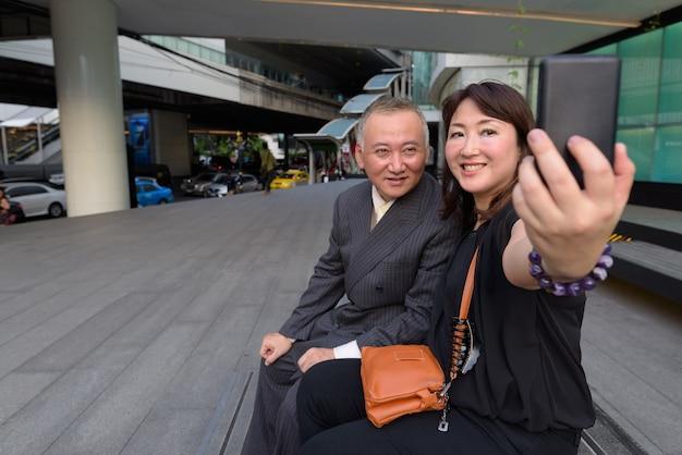 성숙한 일본 사업가와 방콕의 도시를 탐험하는 성숙한 일본 여성의 초상화
