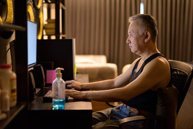 Портрет зрелого японца, использующего компьютер дома