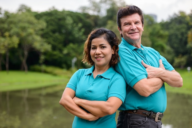 Портрет зрелого мужчины и зрелой азиатской женщины как многонациональной супружеской пары вместе и в любви в парке на открытом воздухе