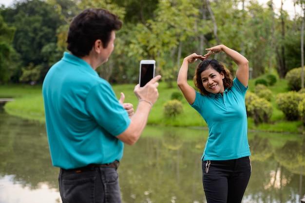 성숙한 남자와 성숙한 아시아 여자의 초상화 멀티 민족 부부 함께 야외 공원에서 사랑에