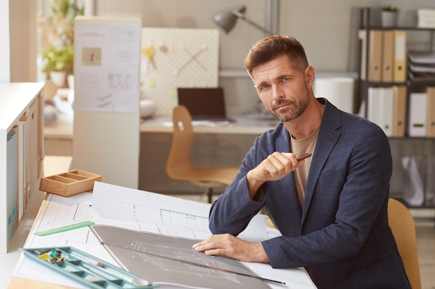 エンジニアのオフィスのデスクで働いている間に青写真と計画を描く成熟した男の肖像画、
