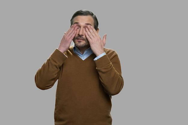 Портрет зрелого мужчины, протирающего глаза. измученный мужчина средних лет на сером фоне.