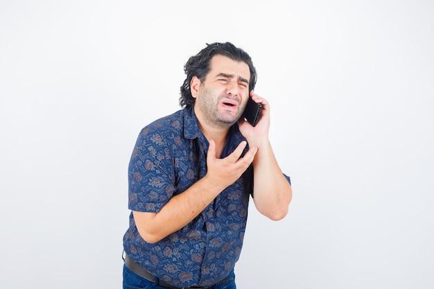 シャツを着て携帯電話で話し、物欲しそうな正面図を見て成熟した男の肖像画
