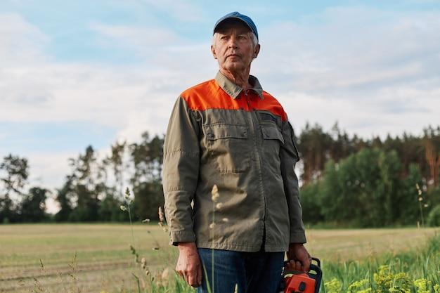 Портрет зрелого мужчины в куртке и кепке позирует на открытом воздухе на лугу с бензопилой в руках