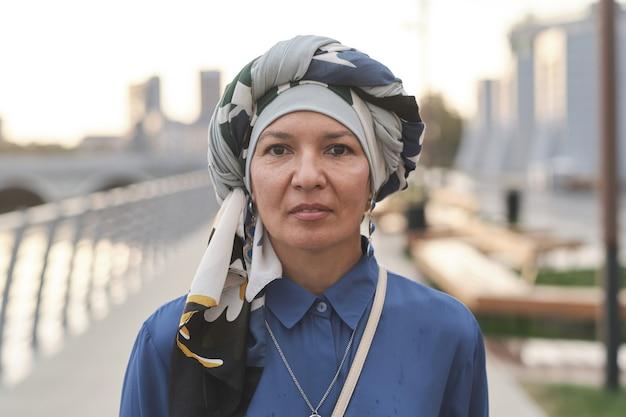 도시에 서 있는 카메라를 보고 있는 머리에 스카프를 두른 성숙한 이슬람 여성의 초상화