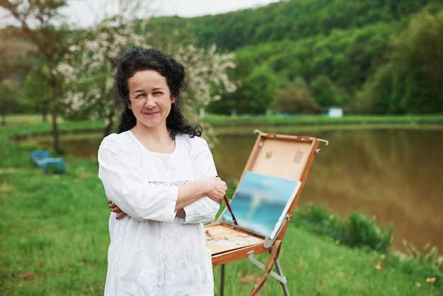 屋外の公園で黒い巻き毛を持つ成熟した画家の肖像