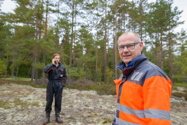 Портрет зрелого скандинавского мужчины и молодого скандинавского мужчины, готовых к сбору урожая в лесу вместе на открытом воздухе