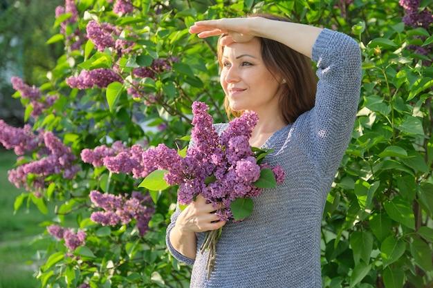 ライラックの花束と庭で成熟した笑顔の女性の肖像画