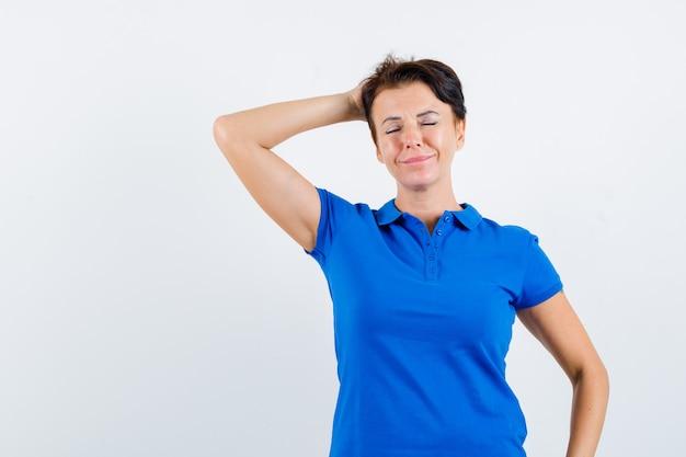 青いtシャツで頭の後ろに手をつないで、平和な正面図を見て成熟した女性の肖像画