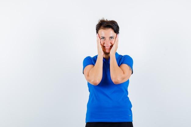 青いtシャツで頬に手をつないで、陽気な正面図を見て成熟した女性の肖像画