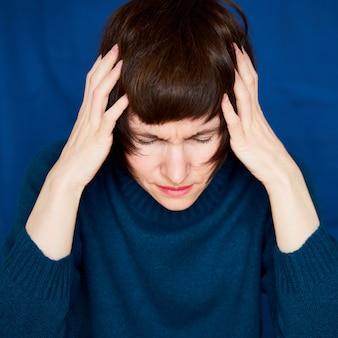 Портрет зрелой женщины в беде крупным планом с возбужденным напряженным лицом на ярко-синей стене