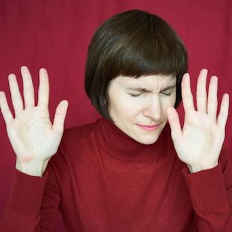 Портрет зрелой женщины в беде, руки вверх, останавливая жест, возбужденное напряженное лицо