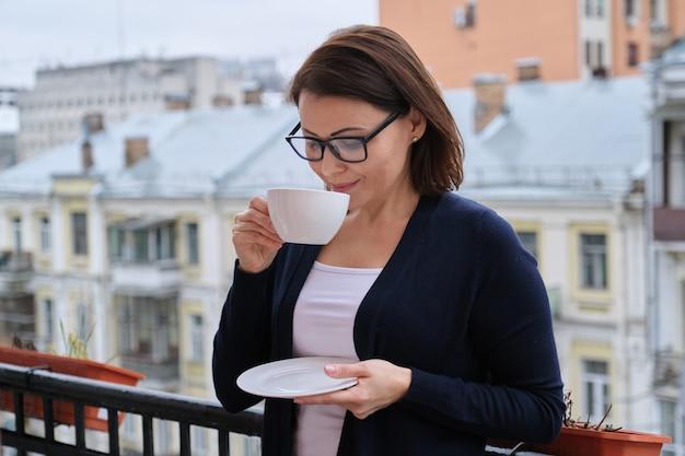 Портрет зрелой женщины в очках, кардигане с чашкой чая на открытом балконе в городе