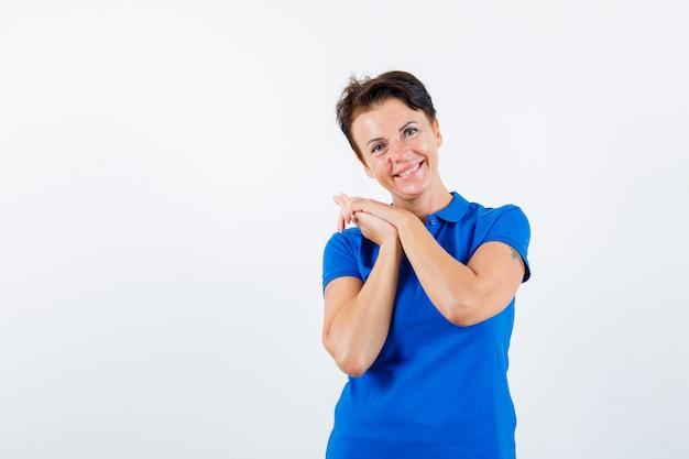 青いtシャツを握りしめ、陽気な正面図を見てポーズをとる成熟した女性の肖像画