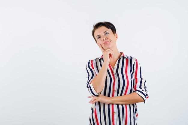 스트라이프 셔츠에 손에 턱을지지하고 잠겨있는 전면보기를 찾고 성숙한 여자의 초상화