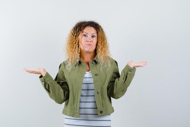 緑のジャケット、tシャツ、無力な正面図で無力なジェスチャーを示す成熟した女性の肖像画