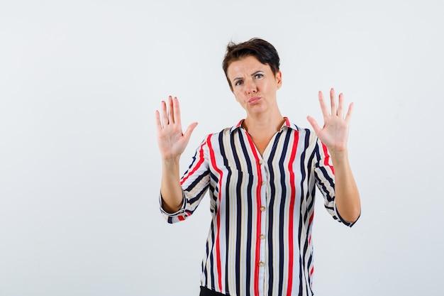 스트라이프 셔츠에 중지 제스처를 표시하고 단호한 전면보기를 찾고 성숙한 여자의 초상화