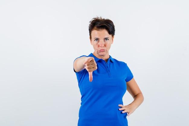 青いtシャツに親指を下に表示し、不機嫌そうな正面図を見て成熟した女性の肖像画