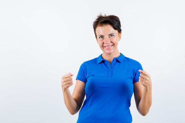 파란색 티셔츠에 승자 제스처를 보여주는 성숙한 여자의 초상화와 행복 전면보기를 찾고