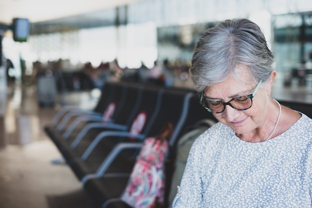 飛行機の出発を待っている携帯電話を使用して荷物を持って空港に座っている成熟した女性の肖像画。コロナウイルスと自由の概念