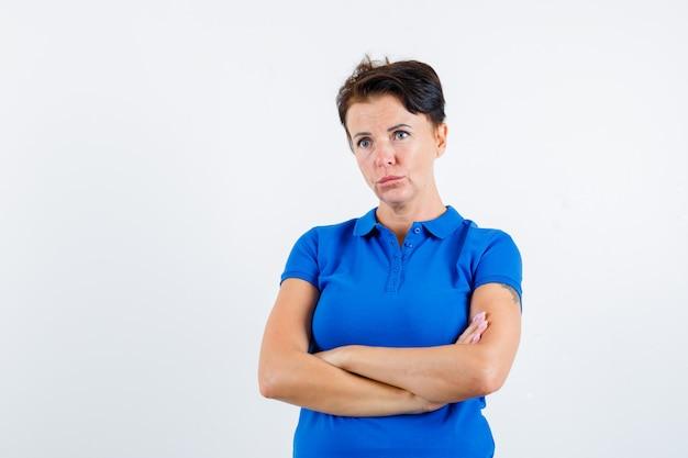青いtシャツと物思いにふける正面図で腕を組んで立っている成熟した女性の肖像画