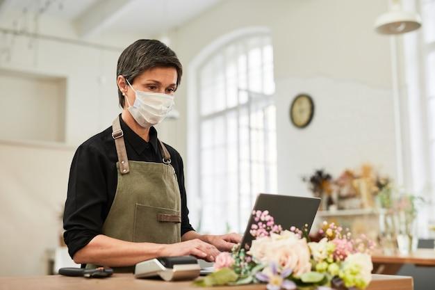 소규모 비즈니스 복사 공간을 관리하면서 꽃가게에서 노트북을 사용하는 성숙한 여성의 초상화