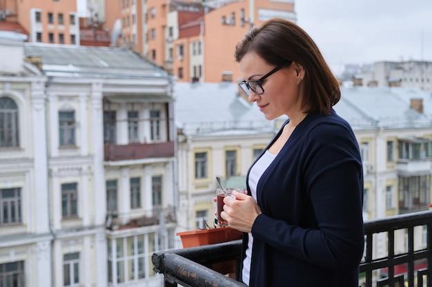 屋外のバルコニーに立っているお茶と成熟した女性の肖像画。街の通り、都市の背景、コピースペースを見ている女性