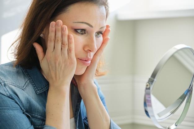 Портрет зрелой женщины с косметическим зеркалом массируя лицо