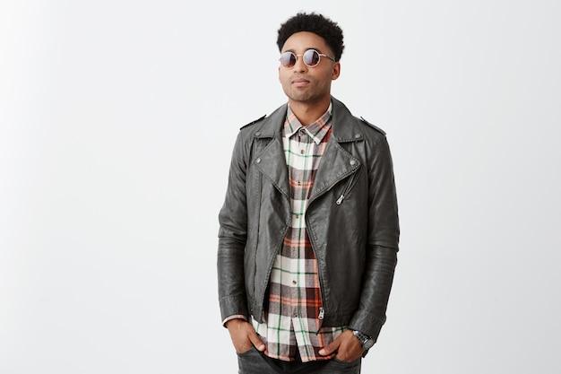 Портрет среднего симпатичного темнокожего парня с афро прической в клетчатой рубашке под кожаной курткой и солнцезащитными очками, держась за руки в карманах, ожидая подругу у кафе.