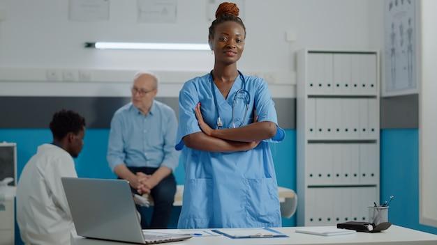 キャビネットに立っている制服を着た医療助手の肖像画