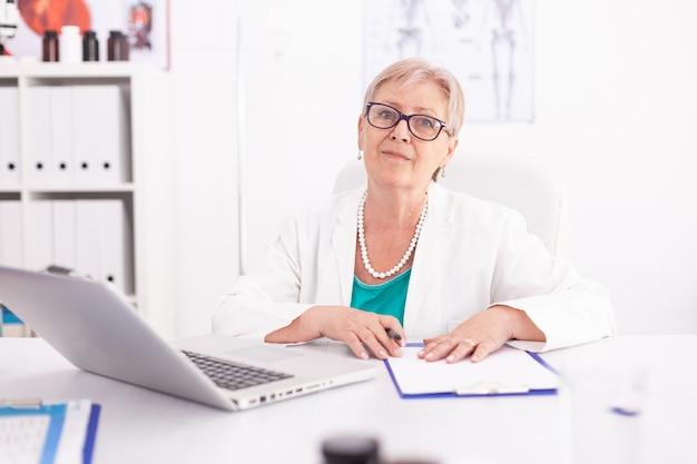 Портрет женщины врача, улыбаясь, глядя на камеру в офисе больницы, носить лабораторный халат. практикующий врач, используя ноутбук на рабочем месте клиники, уверенный, опыт, медицина.