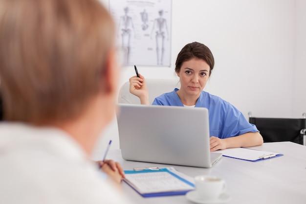 会議室の机に座っている医師と病気の検査について話し合う医療専門医の看護師の肖像画