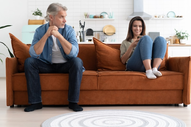 喧嘩の後、ソファに座っている中年のカップルの肖像画。