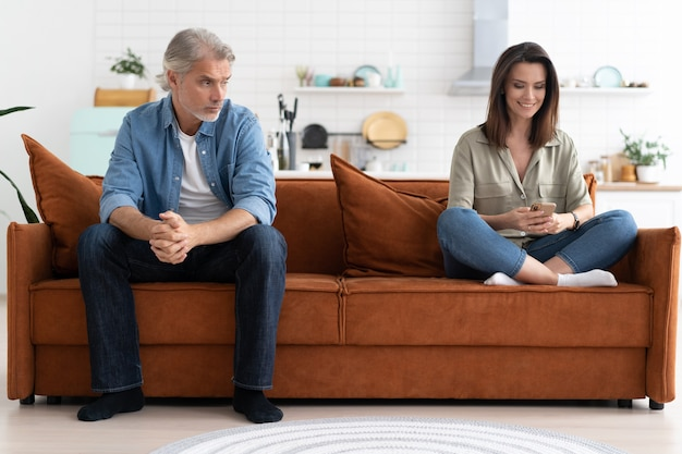 Портрет пары mid-adult, сидя на диване после ссоры.