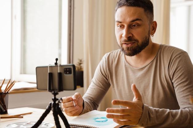 중년 예술가 남성 검은 머리 남자의 초상화는 학생들을 위한 온라인 미술 수업을 하며 행복하게 웃고 있습니다.