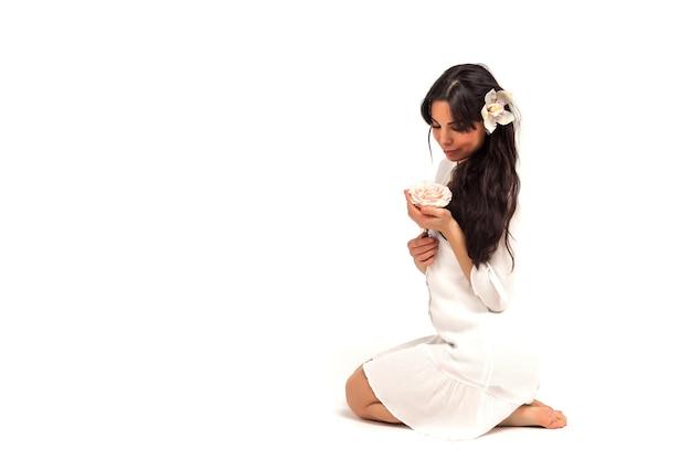 白い孤立した背景に花を持つ中年女性の肖像画。女性はピンクの花を持って、感情的にポーズをとります。美容とパーソナルケアサロンの自然化粧品と広告コンセプト