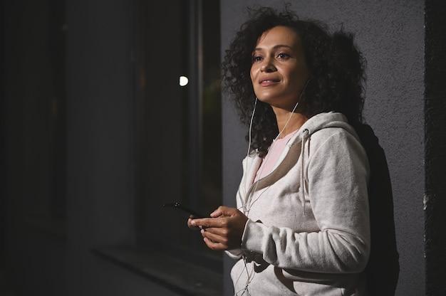 도시 건물의 회색 벽에 기대어 이어폰과 스마트폰을 들고 멀리 바라보는 아프리카 중년 여성의 초상화