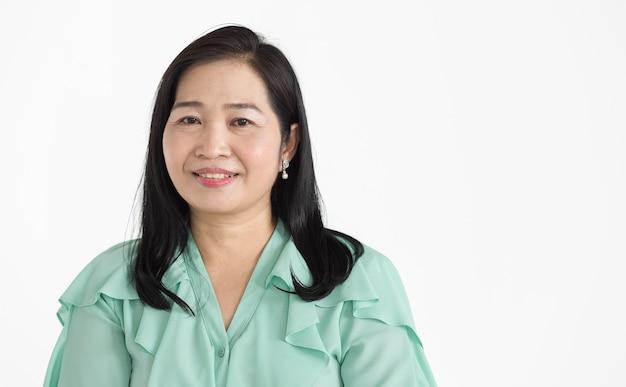 ミントグリーンのブラウスを着て、自信を持って孤立して美しく笑顔できれいに見える中年のアジアの女性の肖像画。