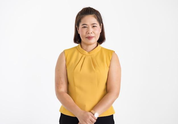 自信を持って孤立して美しく笑っている黄色いブラウスを着ている中年のアジアの女性の肖像画。