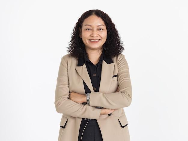 黒のシャツとベージュのジャケットを身に着けている巻き毛の黒い髪を持つ中年のアジアの女性の肖像画は、自信を持って孤立してきれいに笑っています。