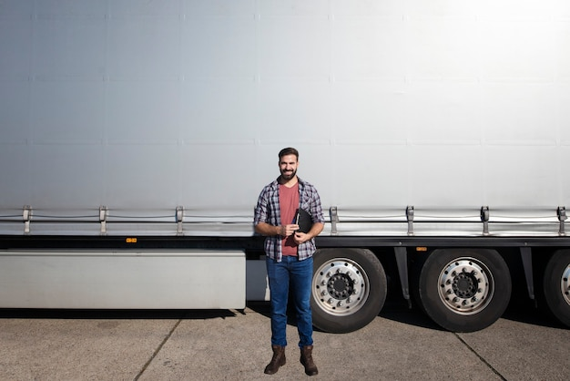 Портрет бородатого дальнобойщика средних лет, стоящего перед прицепом грузовика на фоне серого блестящего брезента