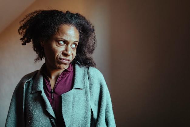 멀리보고 미친 표정으로 중 년 흑인 여성의 초상화. 선택적 눈 초점.