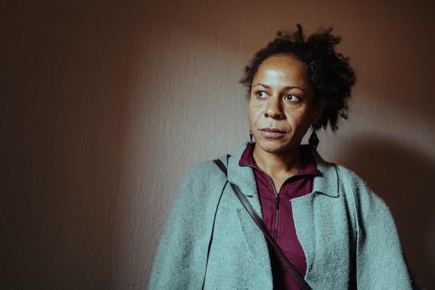 멀리보고 심각한 표정으로 흑인 중 년 여성의 초상화. 선택적 눈 초점.
