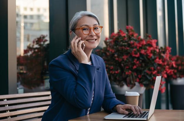 ラップトップを使用して、スマートフォンを持っている、オンラインで作業する中年の実業家の肖像画