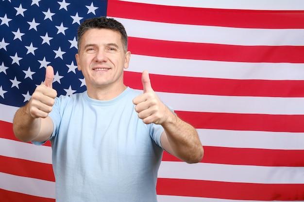 立って、米国旗の背景に親指を押して、カメラを直接見ているカジュアルな青いtシャツを着た中年の白人アメリカ人の男の肖像画。テキスト用のスペースをコピーする